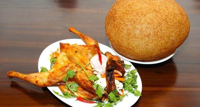 Một đĩa xôi phồng tròn to chiên vàng đều đặn đặt bên cạnh một đĩa gà quay chín thơm, béo